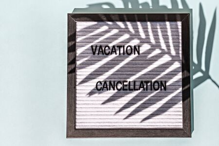 A message Board with the words vacation cancellation on a blue background. On the Board, the shadow of a palm leaf. Concept pandemic coronavirus and the global crisis