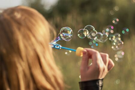 Red-haired girl blows soap bubbles in the park. View from the back