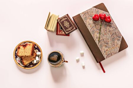 On the table with books, cupcake, marshmallow is a Cup of black coffee and foam in the form of a heart