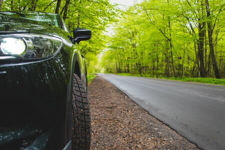 Black car stands on the side of a forest road Stock Photo