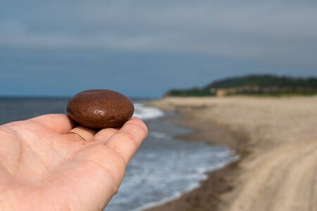 Sea stone in hand on the background of the sea coast