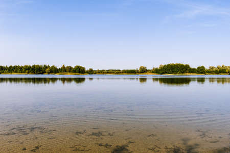 Panoramic view of the lake at noon with green forest on a sunny summer day