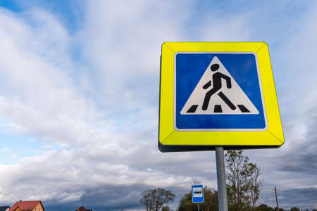 Pedestrian crossing sing on the background of blue cloudy sky Stock Photo