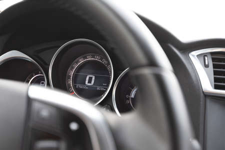 A close-up of the steering wheel and speedometer inside a modern car.