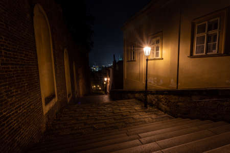 light from a lit street light in a city street stairs at night. glowing lamp at night in the old town of prague in the czech republic