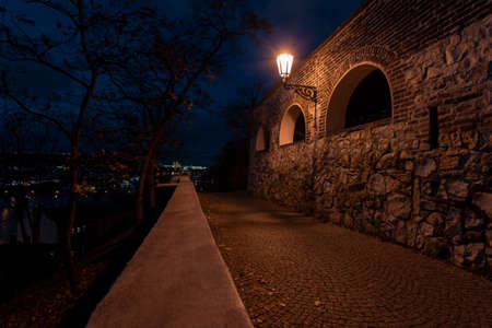 light from a glowing lamp on a stone wall from the 15th century at night in the center of Prague