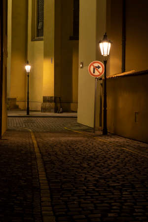 street lights on an illuminated street and pebbles on the ground in the center of the old town of prague at night in the czech republic
