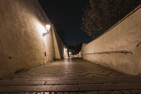 light from street lights and sidewalk and cobblestones on the ground at night in the center of Prague