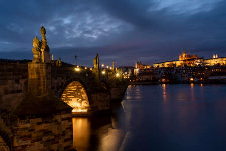 old illuminated prague castle and charles bridge and st. vita church lights from street lights are reflected on the surface of the vltava river in the center of prague at night in the czech republic
