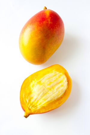 Top view flat lay one whole and halves fresh ripe tropical mango fruit isolated on white background for veggie tables and healthy habits