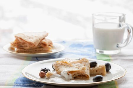 gluten free homemade pancakes plate with sour cream and glass of milk breakfast on white kitchen table snow winter window background copy space
