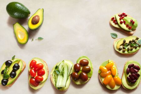 Vegetarian avocado sandwich on white beeswax wraps paper with fresh sliced avocados and vegetables top view flat lay with copy space Banque d'images - 132094986