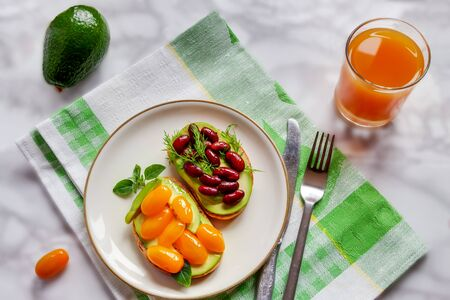 Top view plate vegetarian snack with two fresh sliced avocado sandwiches with red canned fermented beans and yellow tomatoes with orange juice and whole avocado fruit marble table flat lay Banque d'images - 132094985