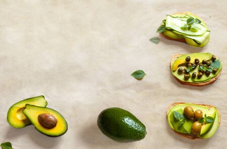 Vegan table avocado toasts isolated on white beeswax paper with fresh sliced whole avocados and green cucumbers, capers, olives flat lay top view . Healthy breakfast and vegetarian food concept Banque d'images - 132095439