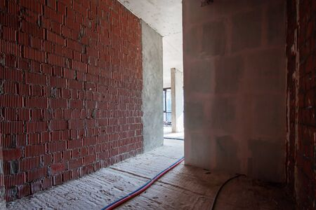 Built structure construction site of residential apartment building with sun bright light in dark narrow red brick wall corridor. Interior in progress to new house with electric colored wires on the floor.
