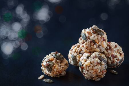Dates homemade organic seeds nuts vegan oatmeal balls with honey. No cook raw vegetarian energy bites, selective focus on black slate of tile with light white silver bokeh lights background Banque d'images - 132242225