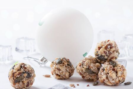 Dates energy homemade no cooked organic seeds nuts vegan oatmeal balls white winter background Reklamní fotografie