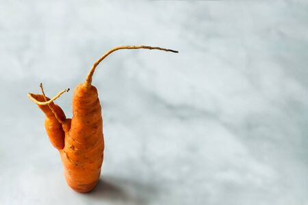 One ugly raw carrot root on the marble kitchen table