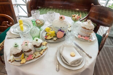 Top view closeup easter table setting sweet baked pastry on tableware white tablecloth with silverware Zdjęcie Seryjne