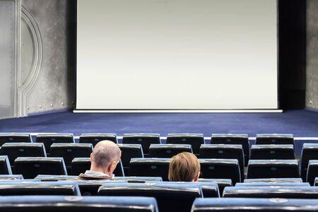 Few people in an empty blue cinema hall waiting unpopular movie