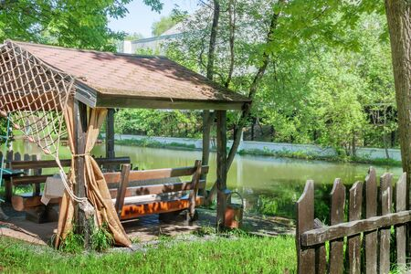 fishing gazebo in garden setting front or back yard on the riverbank under the trees warm spring or summer sunny day Stock fotó