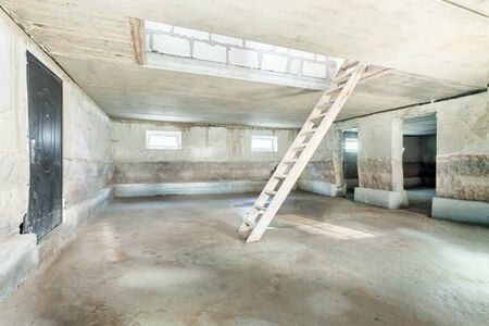 construction site interior of new apartment with windows and wooden ladder middle of the room