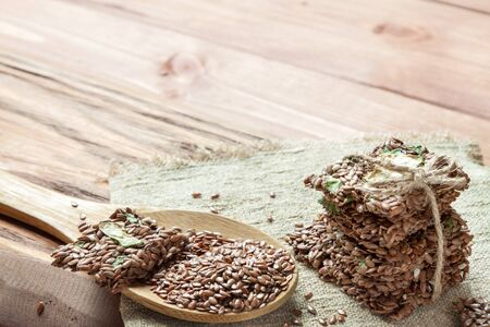 Flat lay top view crunchy flax seed crispbread with dry vegetable and linseed spoon on wooden rustic background with copy space