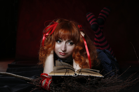 Red-haired girl pozhozhaya on a witch with a broom and an old book.