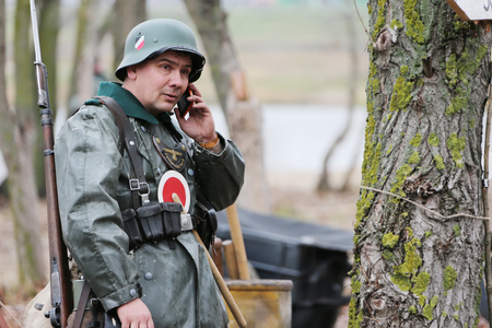Belarus, Gomel, November 21, 2016, Reconstruction of the battle of the Second World War.Soldier of the German army of the Second World War with a cell phone. Reconstruction of battle. German soldier Editöryel
