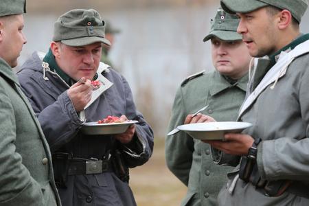 Belarus, Gomel, November 21, 2016, Reconstruction of the battle for World War II. A German soldier of World War II drinks tea. German soldier