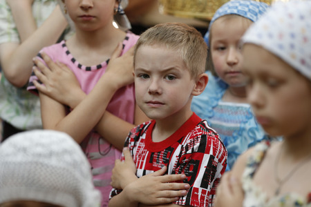 Belarus, Gomel city, St. Nicholas Monastery, a religious Orthodox holiday Palm Sunday 19.06.2016 year. The boy in front of a rite of Communion.Children in the church. Believers Children