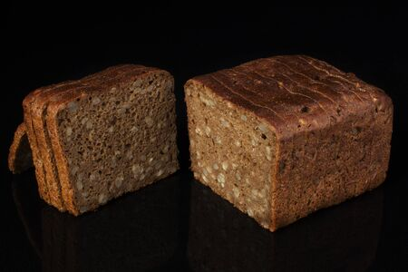 Ordinary bread with grains and sesame cut into pieces on a black background. Whole wheat bread