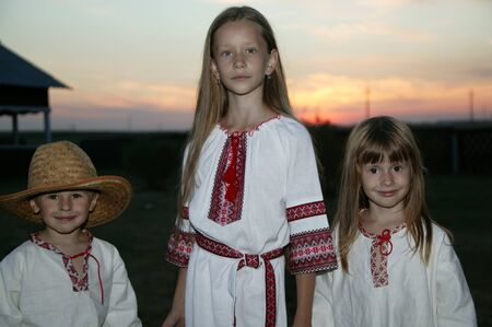 Slavic children in an embroidered shirt on a sunset background. Children are Ukrainian and Belarusians. People in national clothes.