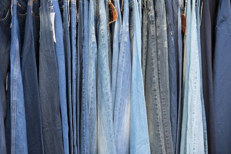 Jeans hang in a row. Pants made of woven fabric Stock Photo