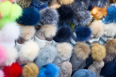 Knitted hats with colored pom-poms
