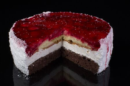 Piece of a large cake in coconut shavings with strawberries in jelly on a black background