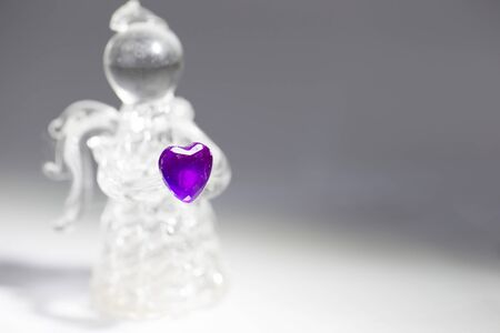Glass angel with a purple heart closeup