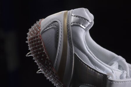 Fragment of a sneaker with spikes on a black background 版權商用圖片