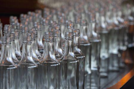 Glassworks. Glass industry. Many glass bottles on a factory conveyor. Standard-Bild