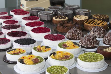 Cake and baking line.Industrial line of cakes. Many beautiful cakes on the table.Multicolored culinary products