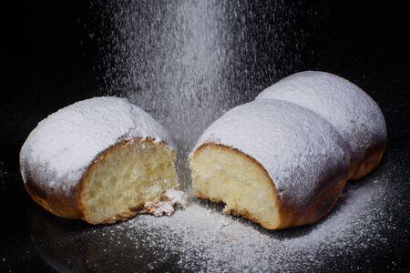Bun with powdered sugar powder on a dark background Archivio Fotografico