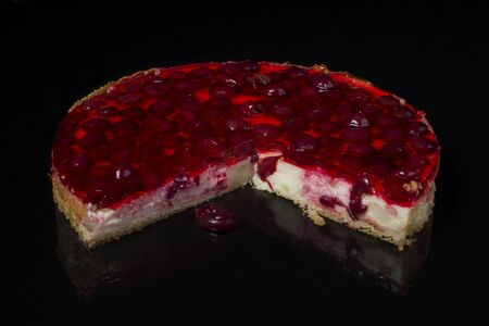 Piece of cake cheesecake with cherry in jelly on black background