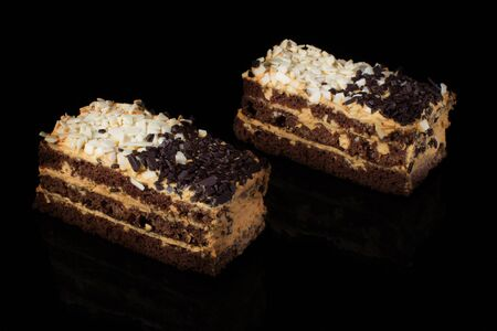 Piece of cake with white and black chocolate on a black background.Russian cake day and night