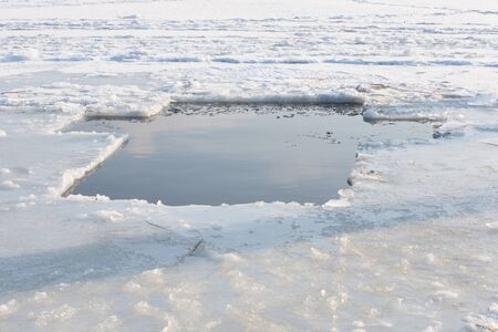 A pond in the icy lake in the form of a cross for the feast of the baptism of the Lord