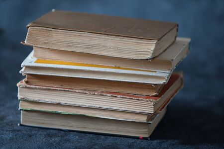 A stack of old books on a gray background. Books