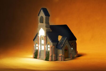 A small children's village house with windows on a dark background. Night cottage miniature closeup
