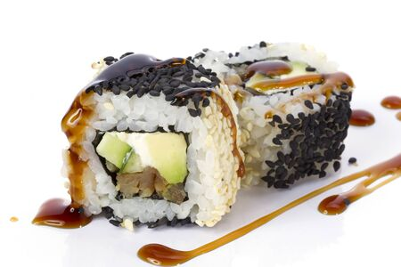 Sushi rolls japanese food isolated on white background.California Sushi roll with tuna, vegetables and unagi sauce closeup.Menu of the Japanese restaurant. Rolls sprinkled with sesame black Stock Photo