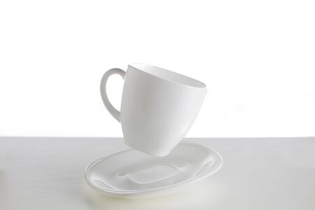White cup with saucer in a jump on a white background. Jumping cup. Flying dishes on a white background.White dishes on a white background 免版税图像