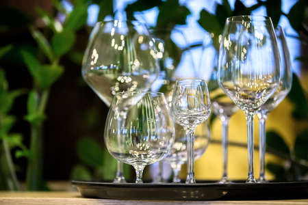 Beautiful empty glass goblets of different sizes. A tray with glasses from a restaurant.