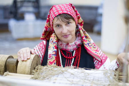 Belarus, Gomel, September 15, 2017. The city's birthday. A Belarusian woman is weaving a towel. Take up weaving. Spin the towel.